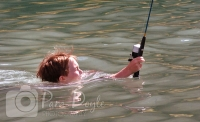 Funny photo of boy fishing and swimming