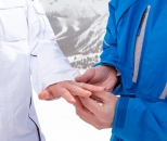 Close up of groom giving bride ring on ski hill