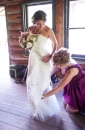 bridesmaid-helps-bride-dress