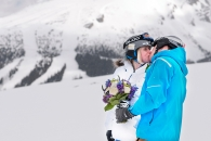 Snowboarders kiss on ski run