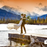 Banff winter wedding with blue sky, mountain views and quaint log bridge